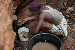 Zokotu Woman scooping drinking water for herfamily