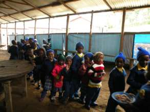 kids eat in a makeshift dining shelter