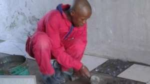 A trainee learning to lay tile