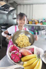 Indigenous Child helping with cutting fruit
