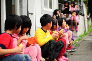 Line of children eating freshly prepared lunch