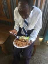 A man Eating at a Food Distribution after church!