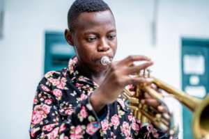 A DCMA student learns to play the trumpet