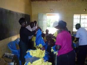 Project director - Mary Goretti distributing unifo