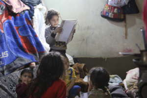 Syrian girl studying in her tent
