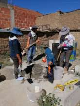 Alejandra, Angela and two helpers mix the concrete