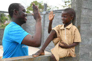 UNICEF staff member with a boy at his new school