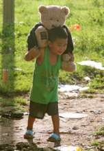 Survivor child carries a friend to safety