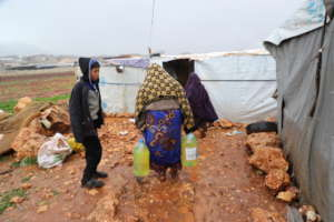 Women enter their tent holding heating fuel