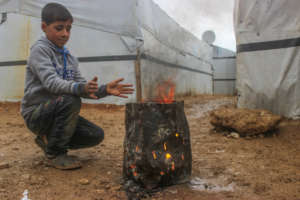 A refugee kid warming his hand
