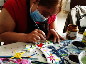 Andrea painting a wooden cross
