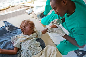 A doctor takes care of a young cholera patient.
