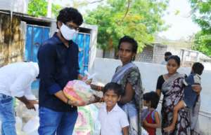 Project leader distributing the releif in a slum