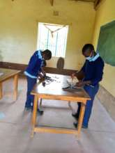 Students repairing one of their woodwork tools