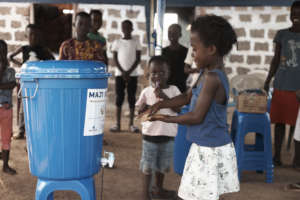 Little girl washes her hands at a Maji Bucket