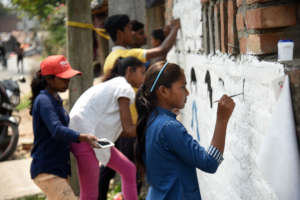 Youth paint informative murals about COVID-19