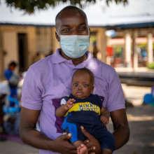 PIH doctor holds baby Naphtal in Sierra Leone