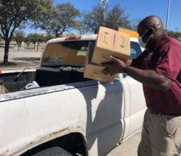 Volunteer loads truck at HISD distribution.