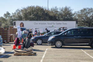 Cars wait in line at NRG Stadium distribution.