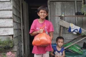 Two siblings receiving YUM's food package