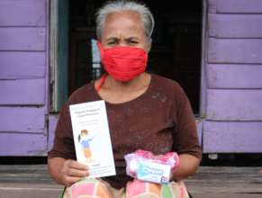 An elderly receiving masks, soaps and a flyer