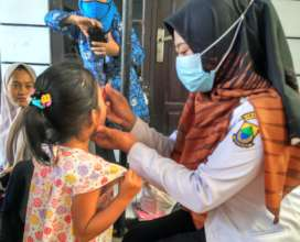 A nurse giving a child deworming treatment