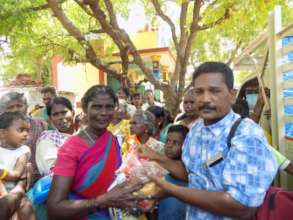 Beneficiary receiving Groceries and Sanitation kit