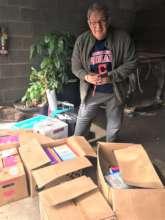 Director Santoli with donations at AAI warehouse