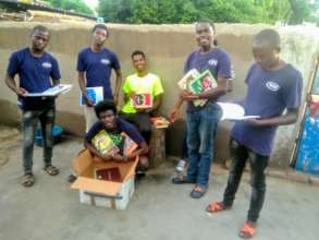 Tweens donating books in camp