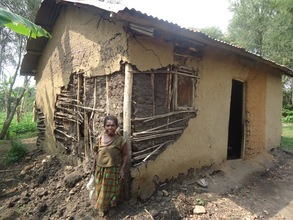 Aidah standing in front of her house