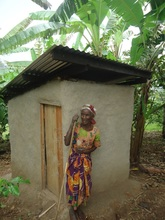 Christine standing with her new pit latrine