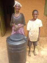 Jane & Grandchild With Their Water Harvesting Tank
