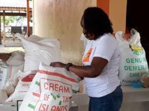 Volunteer Tracy packaging food to distribute
