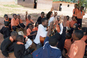 BeeHive teacher leads music group outside.