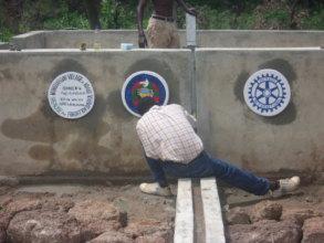 Artist Kodjo paints logos of BARKA-rotary well