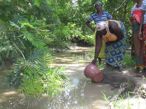 Woman collecting drinking water from dirty stream