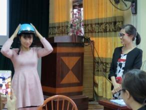 A teacher in Hanoi shows how to wear a helmet.