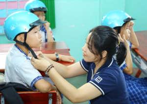 A volunteer helps adjust a student's helmet.