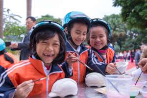 Students enjoy painting helmet sculptures.