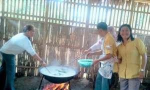 Parents and volunteers prepare meals for children