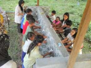 Children wash hands in new school wash facility