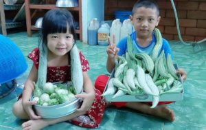 The children adorned with squash from our garden