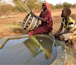 Women softening reeds at well