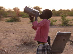 Child drinks water pumped from village well
