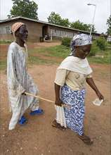 A woman leading a blind patient