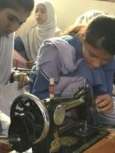 Two young girls who are learning to sew