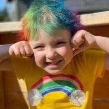 Wish kid Olivia with rainbow hair & a yellow shirt