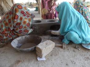 women making cooking stove