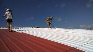 Volunteers work on roof preparation