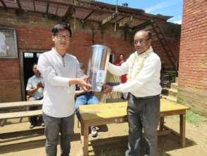 Handing over water filter to school representative